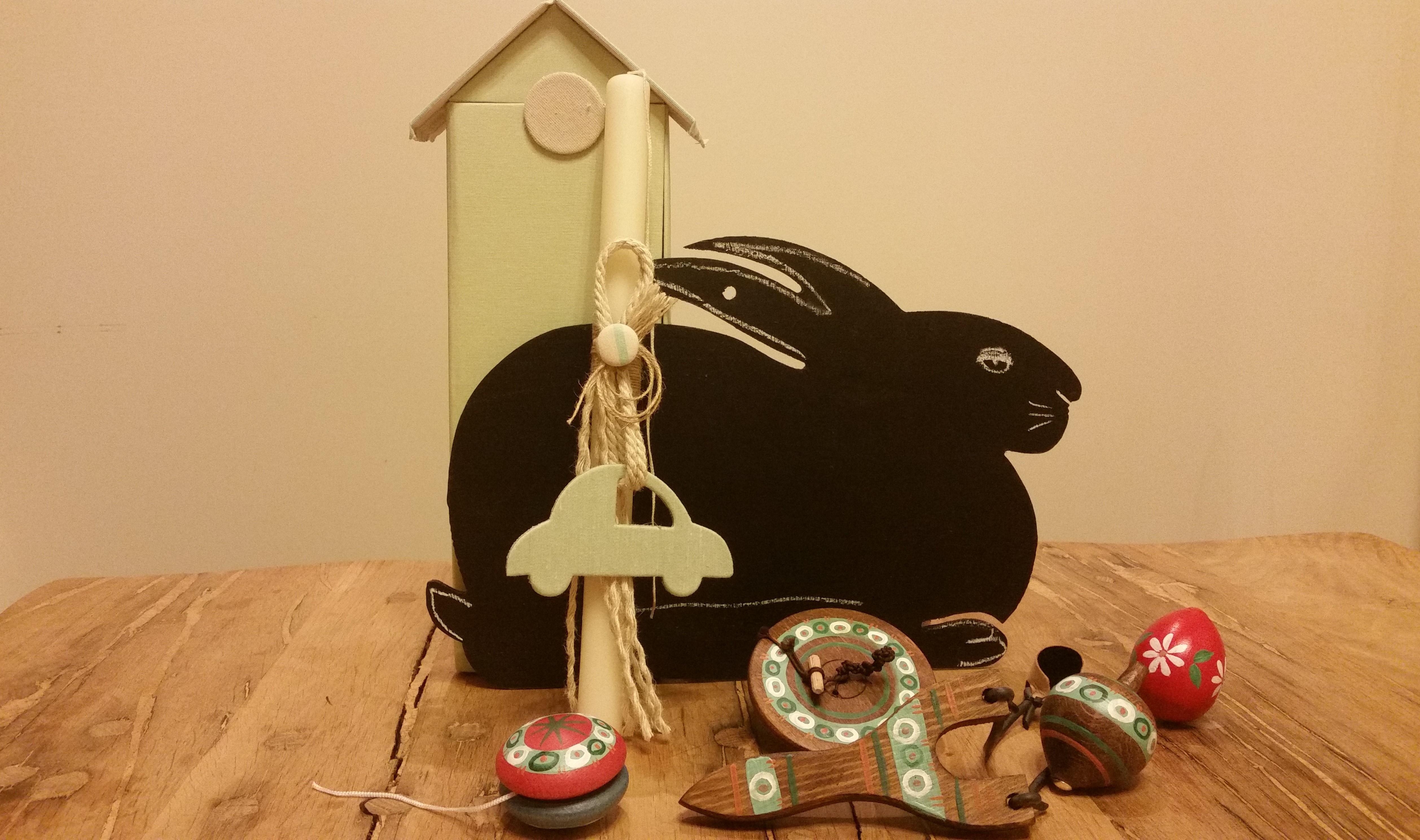"""Πρόταση για δώρο για αγόρια: μεγάλη λαμπάδα με αυτοκίνητο στο """"λαμπαδόσπιτο"""" της, παραδοσιακά παιχνίδια (γιο-γιο, κουμπί, σβούρα, σφεντόνα), ξύλινος μαυροπίνακας σε σχήμα κουνελιού, ξύλινο ζωγραφιστό αυγό."""